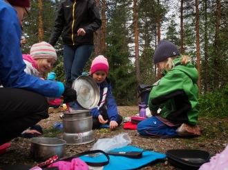 Karhut-ryhmä valmistaa nakkikeittoa.